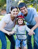 Маленькая девочка, научиться ездить на велосипеде со своими родителями — Стоковое фото
