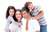 Smiling parents giving their children a piggyback ride — Stock Photo