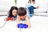 Excited children playing video games lying on the floor — Stock Photo