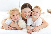 Happy mother and her children lying on a bed — Stock Photo