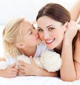 макро блондинка маленькая девочка, целуя ее мать — Стоковое фото