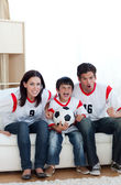 Animated family watching a football match — Stock Photo