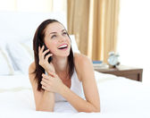 Radiant woman on phone lying on her bed — Foto Stock