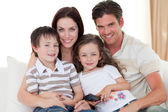 Young family watching TV on the sofa — Stock Photo
