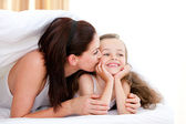 Attentive mother kissing her daughter — Stock Photo