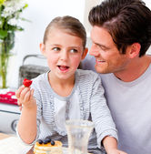 Smiling father and his daughter having breakfast together — Stock Photo