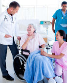 Confident medical team taking care of a senior woman — Stock Photo
