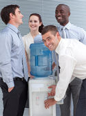 Busines colleagues talking around water cooler — Stock Photo