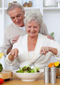 Happy senior couple eeating a salad in the kitchen — Stock Photo