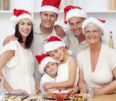 Smiling family baking Christmas cakes — Stock Photo