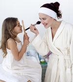 母亲与她的女儿应用腮红 — 图库照片