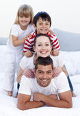 Happy family playing in bed together — Stock Photo