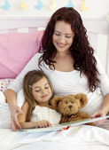 Happy mother and daughter reading in bed — Stock Photo