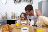 Little girl enjoying her breakfast with her father — Stock Photo