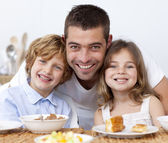 Portrait of children having breakfast with their father — Stock Photo