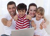 Famille à la maison à l'aide d'un ordinateur portable avec les pouces vers le haut — Photo