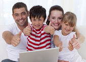 Family at home using a laptop with thumbs up — Stok fotoğraf