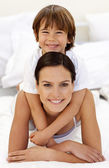 Son hugging his mother in bed — Stock Photo