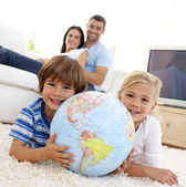 Children playing with a terrestrial globe at home — Stockfoto