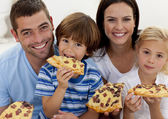Portrait of family eating pizza in living-room — Stock Photo