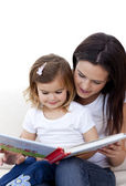 Mother and daughter reading a book on sofa — Stock Photo