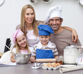 微笑家长帮助孩子在厨房里烘烤 — 图库照片