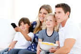 Smiling family watching a film at television — Stock Photo