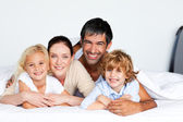 Smiling family together on bed — Стоковое фото