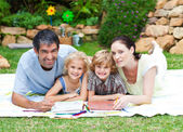 Happy family painting in a park smiling at the camera — Stock Photo