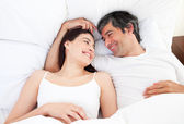 Enamored couple hugging lying in their bed — Stock Photo
