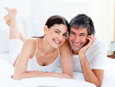 Enamored couple embracing lying on their bed — Stock Photo
