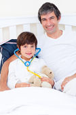 Smiling father and his sick son playing with a stethoscope — Stock Photo