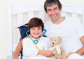 Cheerful father and his sick son playing with a stethoscope — Stock Photo