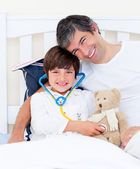 Attentive father and his sick son playing with a stethoscope — Stock Photo