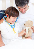Caring father and his sick son playing with a stethoscope — Stock Photo