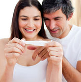 Blissful couple finding out results of a pregnancy test — Foto Stock