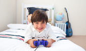 Cute little boy playing video games — Stock Photo