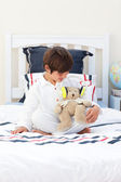 Cute little boy playing with a teddy bear — Stock Photo