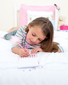 Concentrated Little girl writing on a notebook — Stock Photo