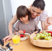 Jolly mother and her child having breakfast — Stock Photo
