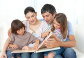 Attentive parents reading with their children — Stock Photo