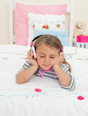 Beautiful Little gril listening to music lying on her bed — Stock Photo