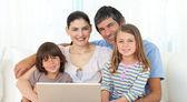 Happy family using a laptop on the sofa — Stock Photo