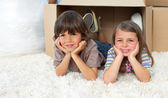 Cute siblings playing with boxes — Stock Photo