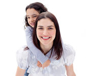 Happy mother giving her daughter piggyback ride — Stock Photo