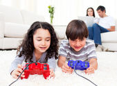Cute siblings playing video games laying down on the floor — Stock Photo