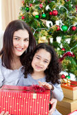 Mother and daughter at home holding a Christmas gift — Stock Photo