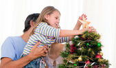 Little girl placing a star in a Christmas tree — Stock Photo