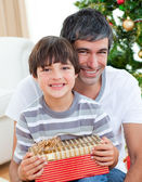 Father and son holding a Christmas gift — Stock Photo