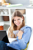 Jolly woman shopping on-line lying on a sofa at home — Stock Photo